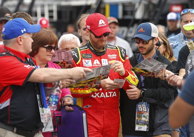 dale-earnhardt-jr-signs-autographs-in-the-garage-before-practice-for-the-nascar-cup-series-auto-race-in-brooklyn-mich-saturday-aug-12-2017