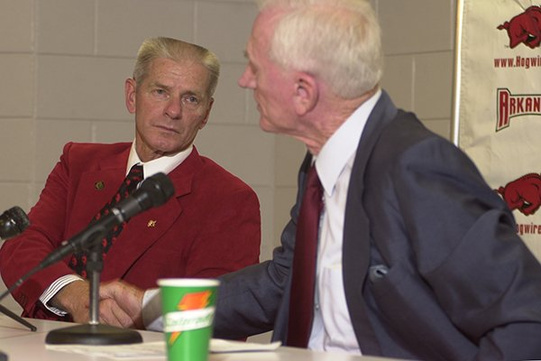 Arkansas baseball coach Norm DeBriyn, left, shakes hands with athletics director Frank Broyles after DeBriyn announced his retirement Tuesday, May 6, 2002, in Fayetteville.