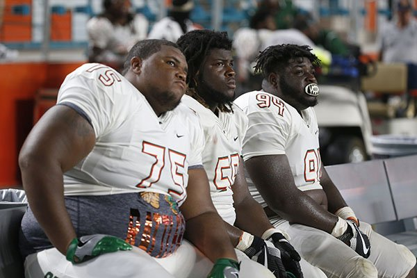 Florida A&M offensive lineman Keenen Anderson (75) linebacker Emilio Gibbs, center, and defensive tackle Javon Hunt (94) watch from the bench during the final minutes of an NCAA college football game against Miami, Saturday, Sept. 3, 2016 in Miami Gardens, Fla. Miami defeated Florida A&M 70-3. (AP Photo/Wilfredo Lee)