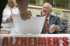 """Arkansas athletics director Frank Broyles signs a copy of """"Coach Broyles' Playbook for Alzheimer's Caregivers"""" on Tuesday, July 18, 2006, at the Walmart on Cantrell Road in Little Rock."""