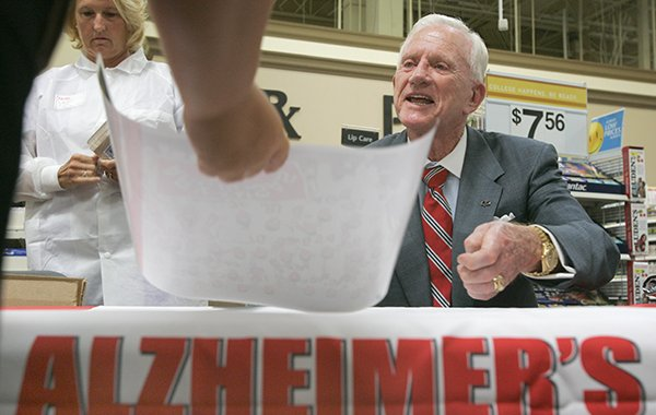 "Arkansas athletics director Frank Broyles signs a copy of ""Coach Broyles' Playbook for Alzheimer's Caregivers"" on Tuesday, July 18, 2006, at the Walmart on Cantrell Road in Little Rock."