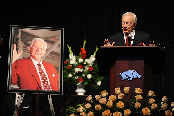 Jerry Jones, former Arkansas player and owner of the Dallas Cowboys, speaks alongside a portrait of Frank Broyles Saturday, Aug. 19, 2017, during a celebration in Bud Walton Arena on the University of Arkansas campus in Fayetteville for the life of Frank Broyles, the former coach and athletics director, who died Monday at 92.