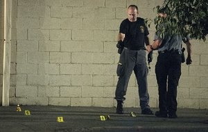 A police forensics team searches for and tags evidence Friday in Fairchance, Pa., where two state troopers were shot.