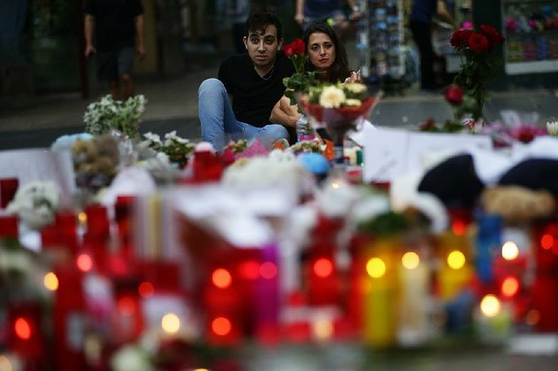 a-couple-in-barcelona-spain-look-over-a-memorial-of-flags-messages-and-candles-saturday-at-the-scene-of-fridays-terrorist-attack-when-a-van-driver-killed-at-least-13-people