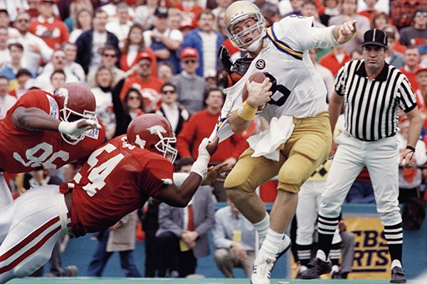 UCLA quarterback Troy Aikman (8) is stopped by Arkansas linebacker Kerry Owens during the second quarter Monday, Jan. 2, 1989, at the Cotton Bowl in Dallas. (AP Photo/Ron Hoflin)