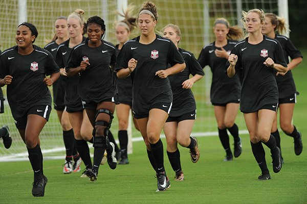 Arkansas soccer players run Wednesday, Aug. 16, 2017, while warming up before the start of practice at Razorback Field in Fayetteville.