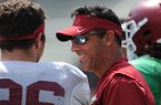 Arkansas offensive coordinator Dan Enos speaks Saturday, Aug. 5, 2017, with linebacker Karl Roesler prior to the start of a scrimmage in Razorback Stadium in Fayetteville.