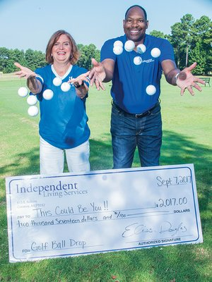 Elissa Douglas, executive director of Independent Living Services in Conway, and Robert Wright, director of development and supportive employment for the nonprofit organization, throw golf balls into the air at Centennial Valley Country Club in Conway. The 12th annual ILS Golf Ball Drop is scheduled from 5:30-7 p.m. Sept. 7. The person whose golf ball is closest to hole will win $2,017. Tickets for numbered golf balls, which will be dropped from a Conway Fire Department bucket truck, can be purchased online at www.indliving.org, at the nonprofit agency at 615 E. Robins St. or at the event.