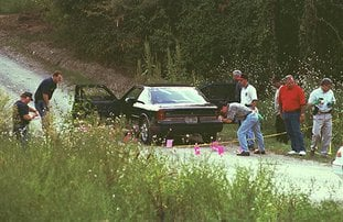 The Sentinel-Record/File photo COLD CASE: Garland County sheriff's investigators, Arkansas State Police and the Arkansas Medical Examiners collect evidence from the scene of a brutal double homicide on Aug. 31, 1997, on Hayti Lane, located just off Bald Mountain Road. The case remains unsolved 20 years later, but investigators are still hoping to bring the killers to justice.