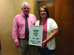 """Norphlet Middle School Principal Keith Coleman and teacher Kim Stanton pose with a sign that reads """"Hurricane Harvey slammed Texas. Be a hero. Donate today. Period 6."""""""