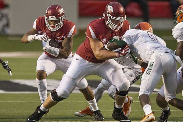 Arkansas running back Devwah Whaley (21) carries the ball behind the block of guard Ty Clary during a game against Florida A&M on Thursday, Aug. 31, 2017, in Little Rock.