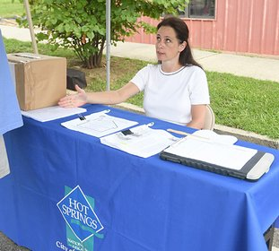 The Sentinel-Record/Mara Kuhn COMMUNITY MINDED: Michelle Sestili, who served as the city's Community Development Block Grant administrator since 2013, staffs a booth at the Community Resource Fair on Aug. 12 in the 100 block of Pleasant Street. Sestili, who is moving with her husband to Houston, left the position Friday.
