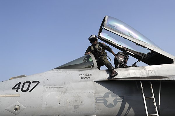 In this Tuesday, Nov. 22, 2016 photo, Lt. Jennifer Sandifer, a 27-year old fighter pilot from Austin, Texas, gets into the cockpit of F/A-18E Super Hornet jet before launching from the deck of the U.S.S. Dwight D. Eisenhower aircraft carrier toward targets in Iraq and Syria. (AP Photo/Petr David Josek)