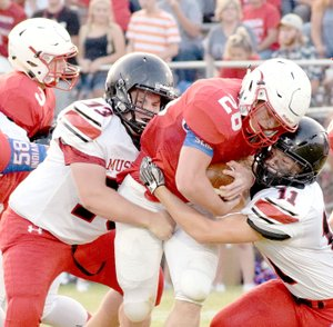 Photo by Rick Peck McDonald County's David Roark (11) and Nolan Baisch (73) team up to stop Seneca's Trey Wilson during the Indians' 41-13 win on Sept. 1 at Seneca High School.
