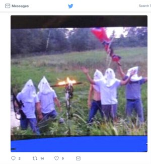 In this screen shot image taken from Twitter, five people wearing white hoods wave a Confederate flag next to a burning cross.