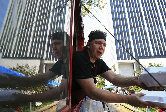 arkansas-democrat-gazettestaton-breidenthal-9817-kyler-nordeck-cq-owner-of-katmandu-mo-mo-delivers-orders-to-customers-friday-during-the-opening-day-of-main-street-food-truck-fridays-at-the-corner-of-capitol-ave-and-main-streets-in-little-rock-sponsored-by-the-downtown-little-rock-partnership-food-trucks-will-be-at-the-location-every-friday-through-oct-27-from-1045-am-until-130-pm-with-the-exception-of-oct-6
