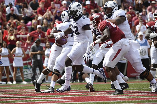 TCU running back Sewo Olonilua (33) slips past Arkansas defender Josh Liddell to score a touchdown in the first half of an NCAA college football game in Fayetteville, Ark., Saturday, Sept. 9, 2017. (AP Photo/Michael Woods)