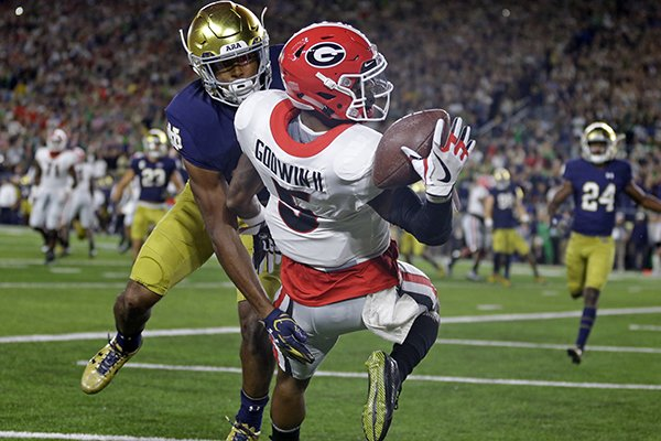Georgia wide receiver Terry Godwin (5) makes a catch against Notre Dame cornerback Julian Love for a touchdown during the first half of an NCAA college football game in South Bend, Ind., Saturday, Sept. 9, 2017. (AP Photo/Michael Conroy)