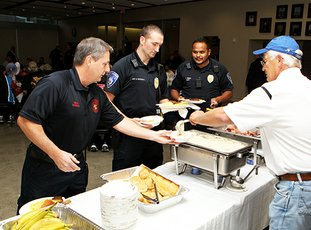 The Sentinel-Record/Richard Rassmussen GIVING BACK: St. Mary's of the Springs Catholic Church member Don Borchert, right, serves breakfast to Hot Springs Fire Department Driver Shannon McDaniel, left, HSPD Officer Shawn Woodall and Officer Richard Nunez during a first responder breakfast sponsored by the Squire Circle 5700 youth group, Knights of Columbus Council 6419 and the congregations of St. Mary's and St. John's churches Monday.