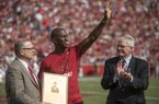 Former Arkansas safety Ken Hamlin, center, receives his UA Hall of Honor plaque from UA athletics director Jeff Long, left, during halftime of a game against TCU on Saturday, Sept. 9, 2017, in Fayetteville.