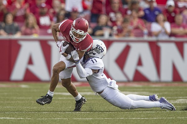 Arkansas receiver Deon Stewart is tackled by TCU defensive back Ranthony Texada during a game Saturday, Sept. 9, 2017, in Fayetteville.