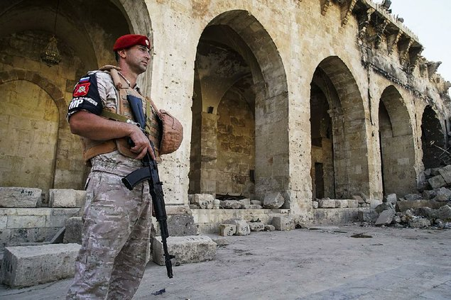 A Russian military police officer stands guard Tuesday in the yard of Aleppo's oldest Umayyad mosque in Syria