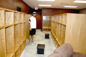 MARK HUMPHREY ENTERPRISE-LEADER Lincoln assistant football coach and head baseball coach Justin Bounds shows off the new varsity football dressing area of the newly constructed Football Fieldhouse at the high school campus. Bounds is making use of the old fieldhouse by conducting workout sessions and weight training for baseball and softball players not involved in fall sports.