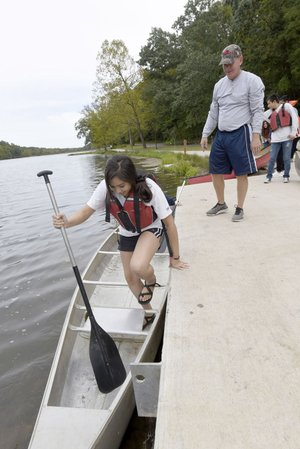 NWA Democrat-Gazette/FLIP PUTTHOFF Ahtziri Maldonado, a student at Heritage High School, boards a canoe Tuesday during an outdoor education class taught by Tom Olsen (right) at Lake Atalanta Park in Rogers. Parts of the park were damaged by flooding in April.