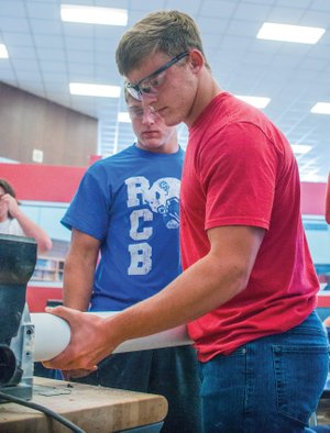Josh Burnham, left, watches his brother, Jack Burnham, sand a piece of plastic pipe for a T-shirt cannon they are making in a pre-engineering class at Arkadelphia High School. A two-day industry fair highlighting jobs in the pre-engineering and manufacturing fields, as well as other skilled professional careers is scheduled for Sept. 27-28 at Arkadelphia High School.