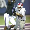 Fayetteville quarterback Darius Bowers (5) passes from his own end zone while Bishop Dunne linebacke...