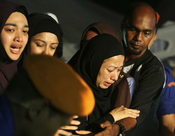 Credit AP  DANIEL CHAN				Relatives mourn Friday during a mass funeral for victims of a school fi re outside of Kuala Lumpur Malaysia