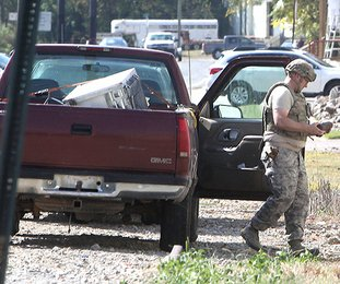 HANDLE WITH CARE: A member of the 19th Civil Engineer Squadron Explosive Ordnance Disposal team from the Little Rock Air Force Base removes a live World War I-era artillery round from the front seat of a pickup truck in the 200 block of Valley Street on Monday.
