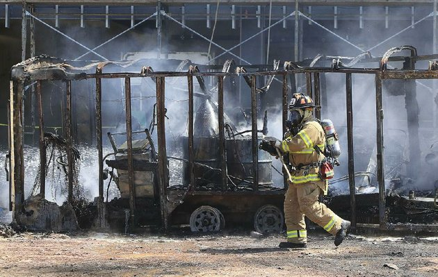 arkansas-democrat-gazettestaton-breidenthal-91917-a-little-rock-firefighter-walks-past-a-smoldering-trailer-tuesday-afternoon-after-firefighters-were-called-to-the-construction-site-for-the-new-midtown-clinic-for-arkansas-specialty-orthopaedic-and-orthoarkansas-at-fair-park-blvd-and-i-630-to-put-out-the-fire