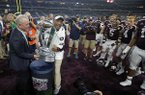 Dallas Cowboys team president Stephen Jones, left, presents Texas A&M head coach Kevin Sumlin with the Southwest Classic trophy after their win against Arkansas in an NCAA college football game, Saturday, Sept. 24, 2016, in Arlington, Texas. (AP Photo/Tony Gutierrez)
