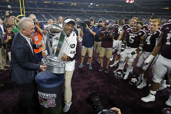 dallas-cowboys-team-president-stephen-jones-left-presents-texas-am-head-coach-kevin-sumlin-with-the-southwest-classic-trophy-after-their-win-against-arkansas-in-an-ncaa-college-football-game-saturday-sept-24-2016-in-arlington-texas-ap-phototony-gutierrez