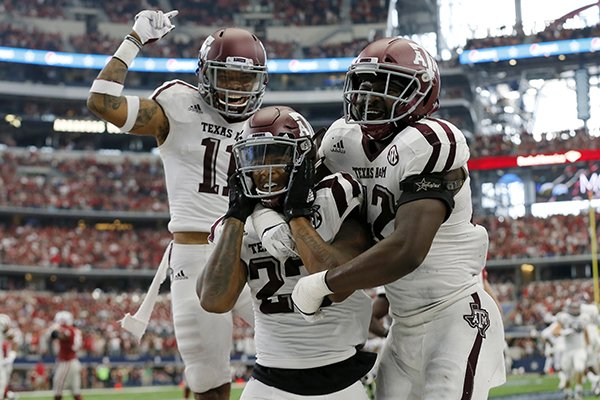 Texas A&M defensive back Larry Pryor, left, defensive back Armani Watts, center, and linebacker Otaro Alaka (42) celebrate an interception by Watts in overtime of an NCAA college football game against Arkansas, Saturday, Sept. 23, 2017, in Arlington, Texas. Texas A&M won 50-43. (AP Photo/Tony Gutierrez)