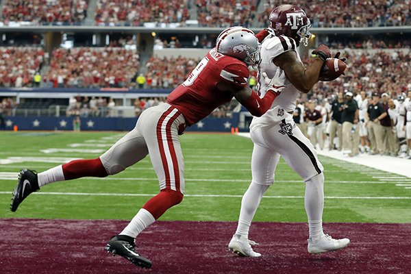 Arkansas defensive back Santos Ramirez (9) defends as Texas A&M wide receiver Christian Kirk (3) catches a pass in the end zone for a touchdown during overtime of an NCAA college football game, Saturday, Sept. 23, 2017, in Arlington, Texas. Texas A&M won 50-43. (AP Photo/Tony Gutierrez)