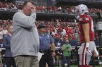 Arkansas coach Bret Bielema, left, waits for players to leave the field following a 50-43 overtime loss to Texas A&M on Saturday, Sept. 23, 2017, in Arlington, Texas.