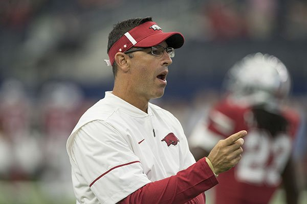 Arkansas offensive coordinator Dan Enos watches warmups prior to a game against Texas A&M on Saturday, Sept. 23, 2017, in Arlington, Texas.