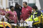 Arkansas coach Bret Bielema, right, talks with Brian Williams, center, and Kim Williams while emergency personnel tend to Rawleigh Williams during a practice Saturday, April 29, 2017, in Fayetteville.