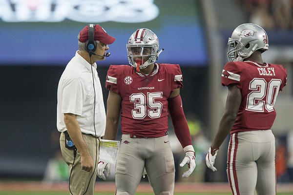 Arkansas defensive coordinator Paul Rhoads, left, talks with linebacker Dwayne Eugene (35) and safety De'Andre Coley (20) during a game against Texas A&M on Saturday, Sept. 23, 2017, in Arlington, Texas.