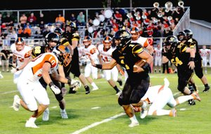 MARK HUMPHREY ENTERPRISE-LEADER Gravette's Austin O'Brien confronts Prairie Grove halfback Anthony Johnson, who carried 13 times for 90 yards and two touchdowns in the Tigers' 31-7 Homecoming win over Gravette Friday.