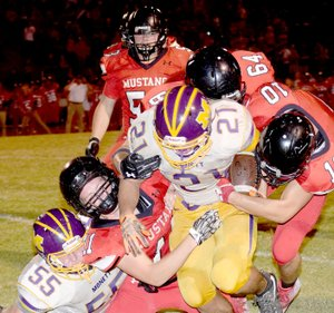 Photo by Rick Peck McDonald County's David Roark (11), Caleb Curtis (10) and Trey Black (64) bring down Monett's Patrick Valentine during the Mustangs 21-18 win on Sept. 29 at MCHS.