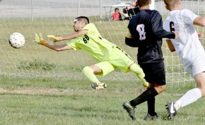 McDonald County goalie Uriel Lazaro dives in an attempt to block a shot during the Mustangs' 5-0 loss to Aurora on Sept. 28 at MCHS.