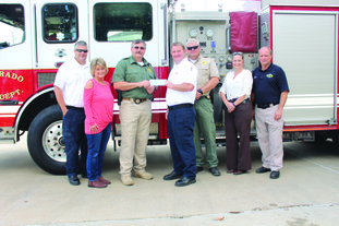 Check presentation: Chief Deputy Charlie Phillips presents Assistant Fire Chief Jesse McKinnon a check from the Union County First Responders Foundation Thursday for his child Braden. From left, Assistant Fire Chief Jason Evans, Jody Cunningham of Union County Judge's Office, Chief Deputy Phillips, Assistant Chief McKinnon, Captain Richard Mitcham, Investigator Tammie Martin and Ken Kelly, CEO of ProMed. Lt. Trey Sewell also received a check from the organization, but was unable to attend the presentation.