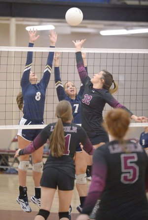 Lincoln's Hollie Webb (32) tries to tip the ball over the net as Shiloh Christian's Kate Turpin (8) and Jentry Lantzsch elevate for the block Thursday in Lincoln. Visit nwadg.com/photos for more photos from the match.