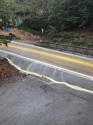 The Arkansas Transportation Department painted stripes on Arkansas 23 through Eureka Springs on Wednesday, but rain quickly washed the yellow paint off the road and into East Leatherwood Creek. (Photo by Damon Henke)