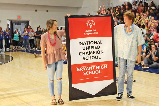 during-a-celebratory-rally-bryant-high-school-students-addie-richards-left-and-jake-cowell-hold-the-banner-specifying-the-special-olympics-distinction-the-school-earned-as-a-national-unified-champion-school