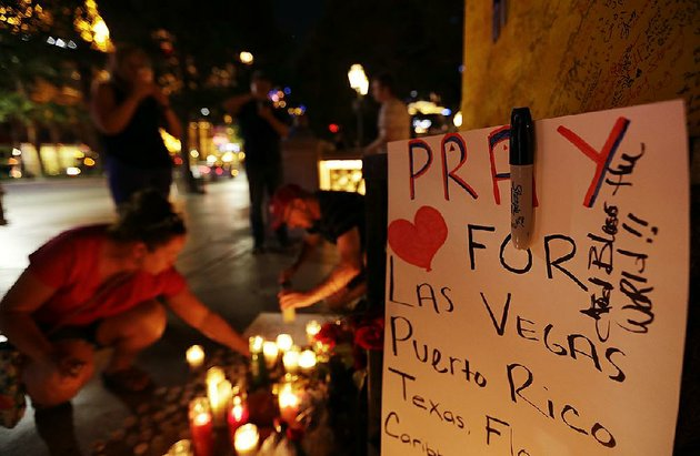 pausing-to-remember-and-reflect-people-surround-a-memorial-set-up-for-victims-and-survivors-of-the-mass-shooting-in-las-vegas-on-tuesday-the-deadliest-mass-shooting-in-modern-us-history-comes-just-after-a-series-of-natural-disasters-in-texas-florida-and-puerto-rico-and-an-earthquake-in-central-mexico-and-has-people-secular-and-of-faith-asking-why-others-suffer