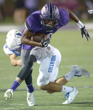NWA Democrat-Gazette/ANDY SHUPE Fayetteville receiver Kris Mulinga (front) tries to break away from Rogers High linebacker Timothy Howard on Friday at Harmon Stadium in Fayetteville. Visit nwadg.com/photos for more photos from the evening's game.